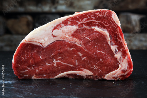 Fotobehang Vlees Raw fresh meat Ribeye Steak, seasoning and meat fork on dark background