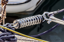 Metal Cleat For Mooring Boats, Bolted To The Ground, With Rope And Shock Absorber Spring