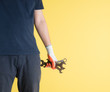 Handyman holding wrenchs on yellow background