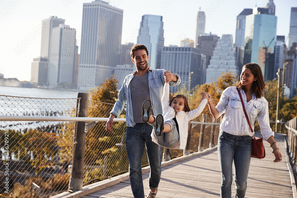 Fototapety, obrazy: Young family with daughter taking a walk on footbridge