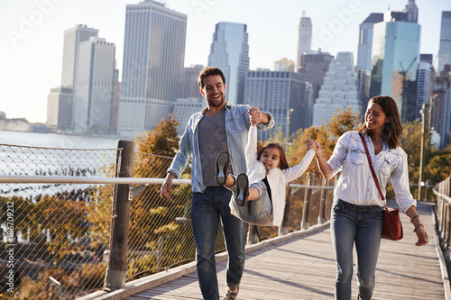 Foto  Young family with daughter taking a walk on footbridge