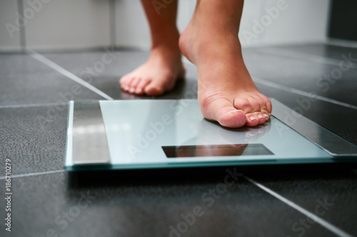 Female bare feet with weight scale in the bathroom Fototapeta