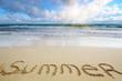 Word Summer written on sand at ocean beach summer time