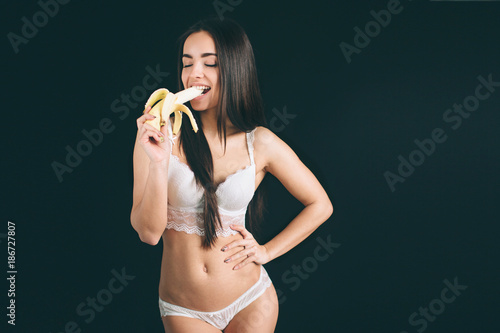 5ea28c19e2f68 portrait of attractive caucasian smiling woman . studio shot eating banana.  Young woman have long black hair ...