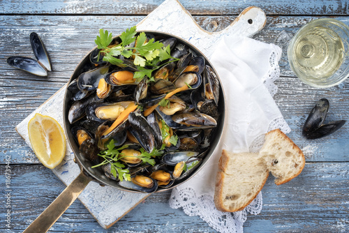 Valokuva  Traditional barbecue Italian blue mussel in white wine as top view in a casserol