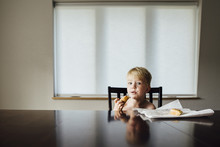 Portrait Of Shirtless Boy Eating Bread While Sitting On Chair At Home