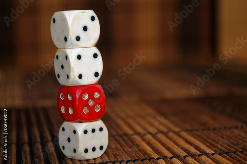 Stack of three white plastic dices and one red dice on brown wooden board background плакат