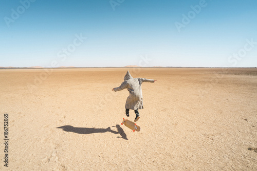 Rear view of man skateboarding on sand against clear blue sky