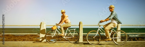 Happy couple riding bicycles on pier Wallpaper Mural