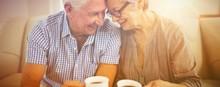 Senior Couple Having Coffee In Living Room