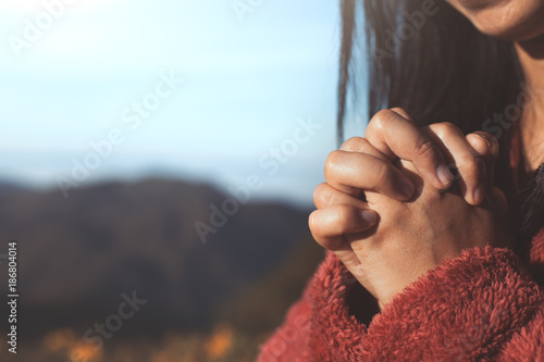Woman hands folded in prayer in beautiful nature background with sunlight in vin Canvas Print
