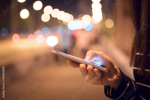 Close up Hand of woman using Mobile smartphone in the street, night light bokeh Background, copy space.