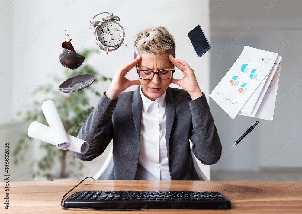 Fototapeta Businesswoman working on a laptop, overworking, under pressure