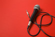 Leinwanddruck Bild - microphone and lead on a bright red background.