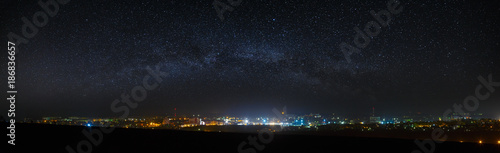 Photo sur Aluminium Nuit Panoramic view of the starry night sky above the city.
