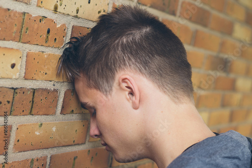 Fotografie, Obraz  Regret cocnept. Sad man leaning his head against the wall.