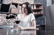 Female alcoholism. Sad cheerless brunette woman sitting at the table and holding a bottle while pouring wine