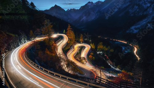 Foto auf Leinwand Gebirge The winding mountain road at the night with light tracks from cars, Maloja Pass, Switzerland