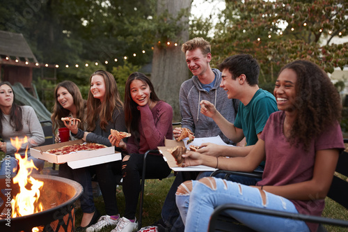 Fotografía  Teenagers at a fire pit eating take-away pizzas, close up