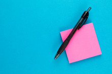 Pink Post With Black Pen On Blue Background