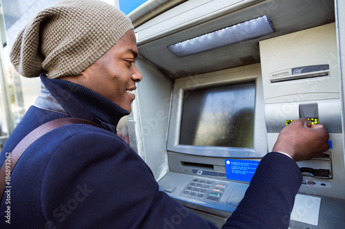 Fotografia, Obraz Handsome young man taking cash from ATM with credit card.