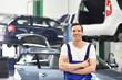 Portrait freundlicher KFZ Mechaniker in einer Autowerkstatt - im Hintergrund Fahrzeuge zur Reparatur auf einer Hebebühne