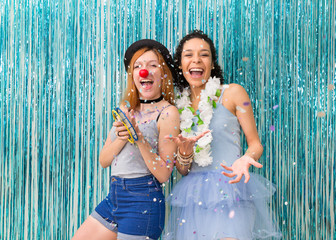Two friends are celebrating Carnaval. Blue color predominant. Confetti..