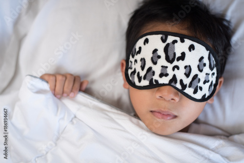 a8ab0f1a0 boy sleeping on bed white pillow and sheets with sleep mask.boy sleeping  peacefully.sleep concept