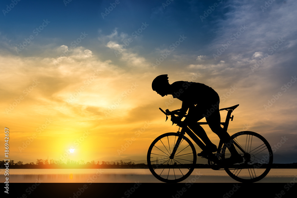Fototapeta Silhouette of man ride a bicycle in sunset background
