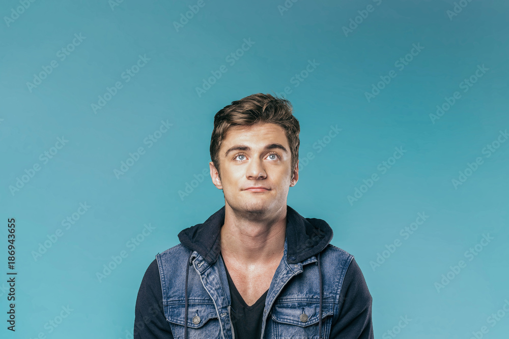 Fototapeta Casual caucasian young man with thoughtful expression