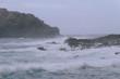 Breaking waves on coastline in dark cloudy weather