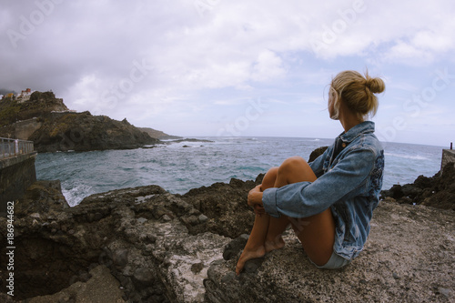 Tuinposter Canyon Young woman sitting on rock and looking at rough sea and breaking waves