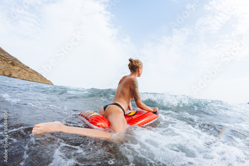 Foto op Aluminium Canarische Eilanden Young topless girl in thongs on pool float in ocean waves