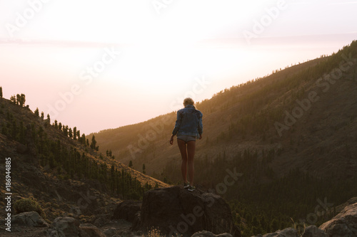 Tuinposter Canarische Eilanden Girl in mini shorts and jeans jacket hiking and looking at sunset in desert nature