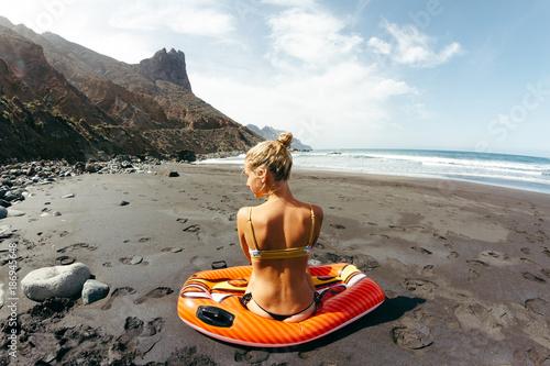 Deurstickers Canarische Eilanden Young girl in thong sitting on beach looking at coastline