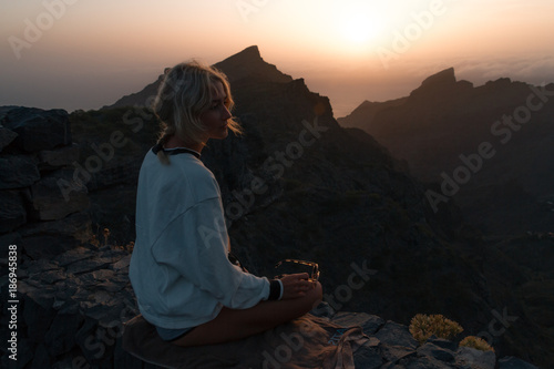 Tuinposter Canarische Eilanden Young blond woman in shorts looking at rocky landscape with steep cliffs while sunset