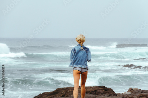 Tuinposter Canarische Eilanden Young fashion woman in jeans jacket and mini shorts posing on coastline with ocean waves in background