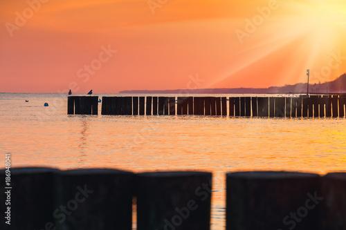 Papiers peints Orange eclat Sunset on the beach with a wooden breakwater, long exposure