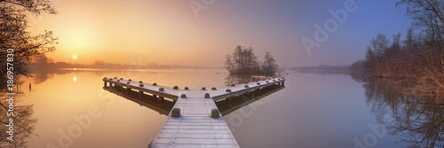 Photo sur Toile Beige Jetty on a still lake on a foggy winter's morning