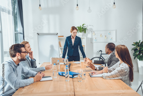 Fototapety, obrazy: businesswoman in formal suit standing against table and speaking to team at office space
