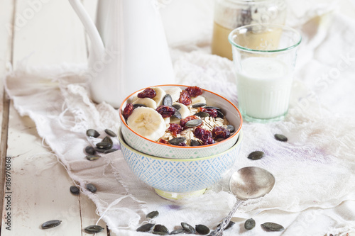 Bowl of oat flakes with dried cranberries, banana slices and pumpkin seed