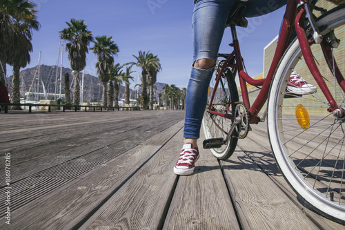 Leg of young woman sitting on bicycle