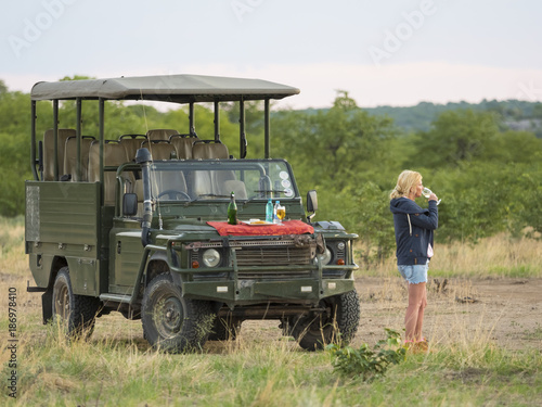 Namibia, Outjo, tourist drinking glass of champagne in Ongava Wild Reservat