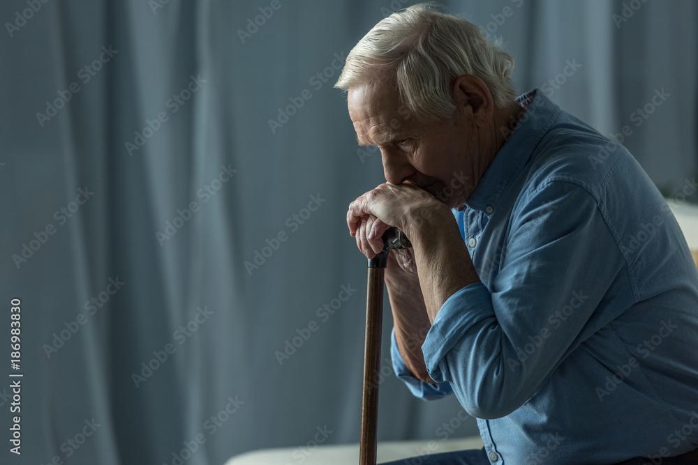 Fototapeta Senior sad man leans on a cane while sitting on sofa