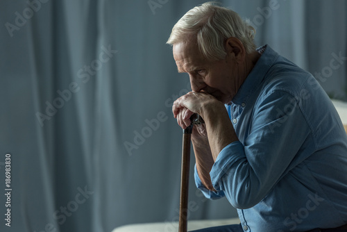 Senior sad man leans on a cane while sitting on sofa Canvas Print