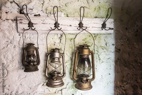 Old vintage storm lamps on stone wall