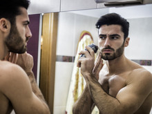 Handsome Young Man Using Shaving Machine At The Mirror.