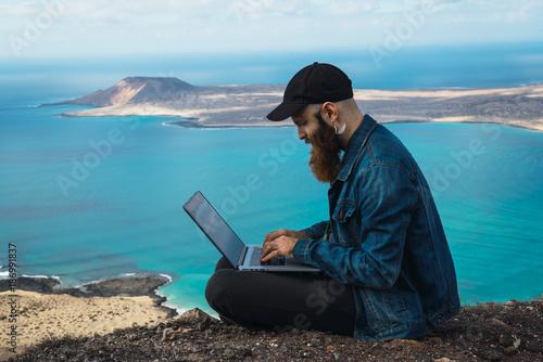 Man with laptop at seaside