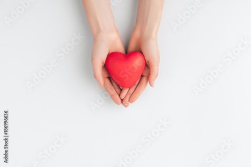 top view of hands holding red heart isolated on white background
