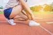 Woman runner tying shoelace on running racetrack